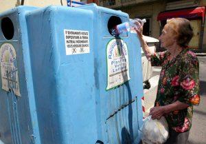 Un'anziana signora getta una bottiglia di plastica nel contenitore della raccolta differenziata in una foto d'archivio. ANSA / FRANCO SILVI