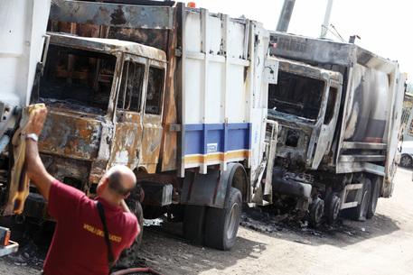 I vigili del fuoco a lavoro sui compattatori dati alle fiamme da sconosciuti a Terzigno (Napoli), la notte tra martedi' e mercoledi' 22 settembre 2010, durante la manifestazione di protesta contro l'apertura della discarica. Anche la scorsa notte sono stati danneggiati camion dei rifiuti. A Boscoreale alcune persone con il volto coperto da caschi hanno incendiato un autocompattatore e hanno riversato l'immondizia in strada. ANSA / PRIMA PAGINA
